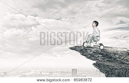 Little joyful cute boy riding tricycle on cliff edge