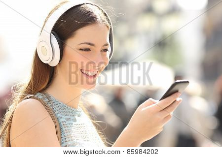 Woman Listening Music From A Smart Phone In The Street