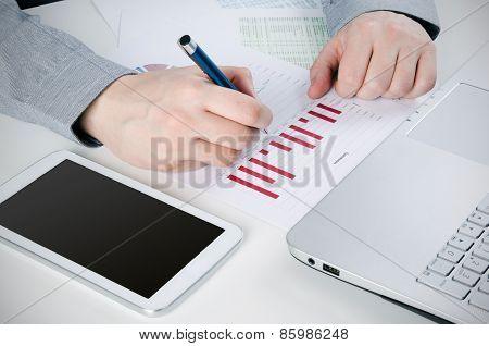 Businessman Working With Digital Tablet. Report Charts On Desk