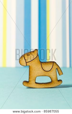 Wooden Icon Of Children's Rocking Horse On Blue Striped Background