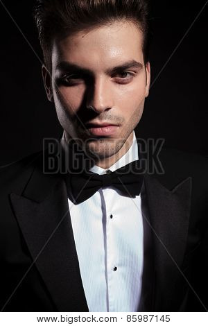Close up picture of a handsome young business man posing on black background.