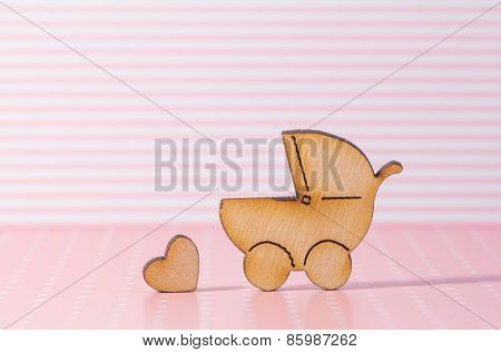 Wooden Icon Of Baby Carriage And Little Heart On Pink Striped Background