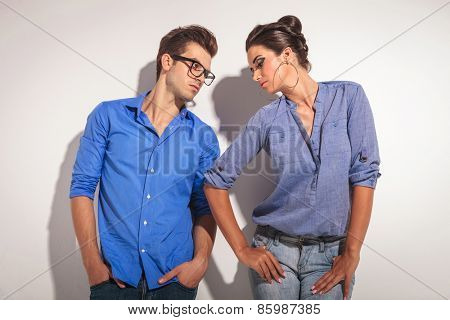 Handsome young man looking at his lover while holding both hands in pockets.