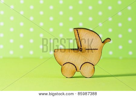 Wooden Icon Of Baby Carriage On Green Background