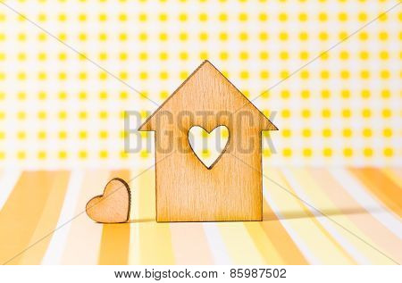 Wooden House With Hole In The Form Of Heart With Little Heart On Yellow Background