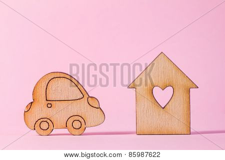 Wooden House With Hole In The Form Of Heart With Car Icon On Pink Background