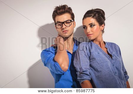 Close up picture of a fashion couple posing on grey studio background. Both looking away from the camera.