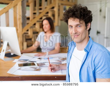 Businessman in office with his collegue at background