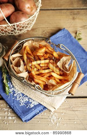 Tasty french fries and fresh potatoes in metal baskets on wooden table background