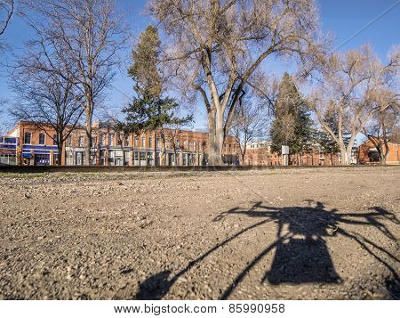 A shadow of quadcopter drone with camera taking off to fly over city