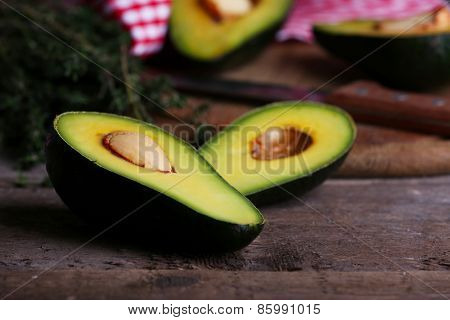 Sliced avocado with lime and herb on cutting board on wooden background