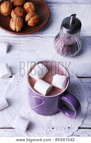 Cup of cocoa with marshmallows and cookies on wooden table, closeup