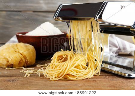 Making vermicelli with pasta machine on wooden background