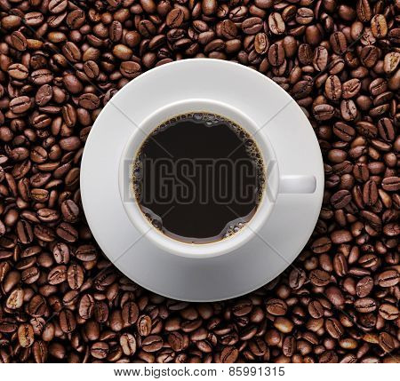 Hot Coffee Cup On Roast Coffee Beans. Top View