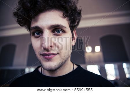 Portrait of a handsome man with curly hair looking at camera
