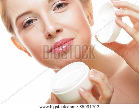 Beautiful spa girl holding jar of cream