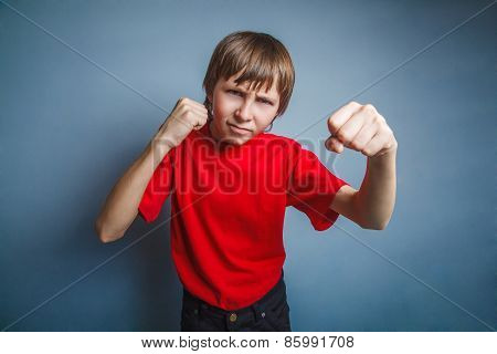 Boy, teenager, twelve years in a red shirt, showing his fists