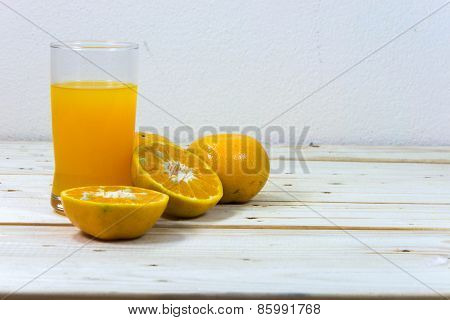 Glass Of Delicious Orange Juice And Slices Of Orange On Wooden Table Background.