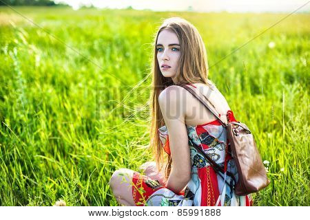 Beautiful woman in dress and bag sitting on the glade