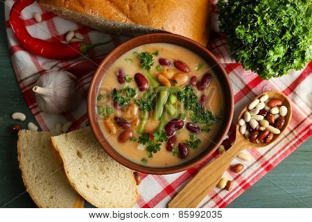 Bean soup in bowl with fresh sliced bread on napkin, on wooden table background