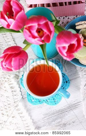 Composition of spring flowers, tea and cookies on table close-up