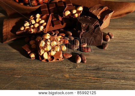 Still life with set of chocolate with nuts on wooden background