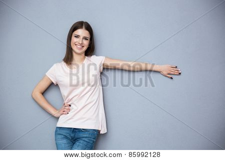 Happy young woman standing over gray background