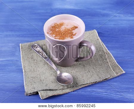 Cup of cocoa with spoon on burlap cloth on color wooden background
