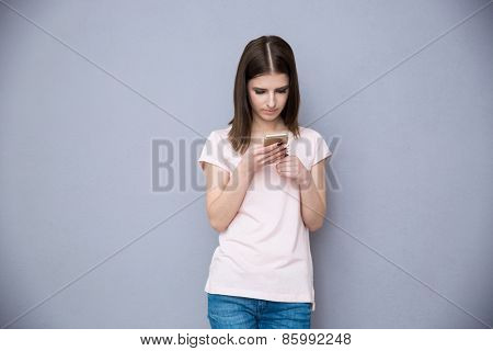 Young woman using smartphone over gray background