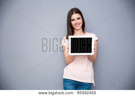 Smiling young woman showing tablet computer screen over gray background