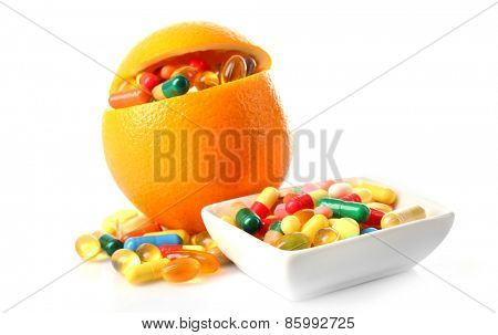 Orange fruit and colorful pills, isolated on white