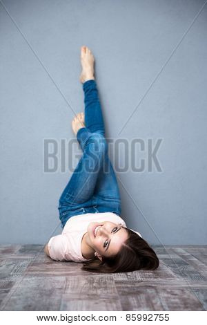 Happy cute woman lying on the floor with legs raised up