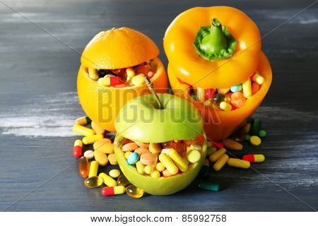Apple, orange, paprika and colorful pills, on color wooden background