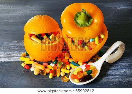 Orange, paprika and colorful pills, on color wooden background