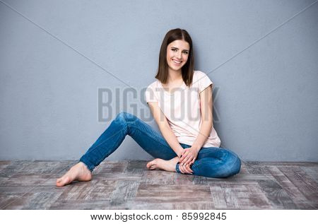 Happy young cute woman sitting on the floor
