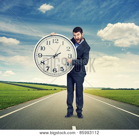 screaming businessman pointing at clock and looking at camera. photo at outdoor