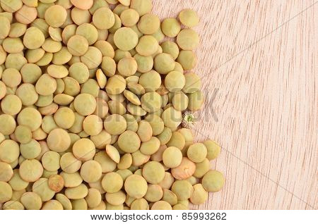 Green lentil on wooden background