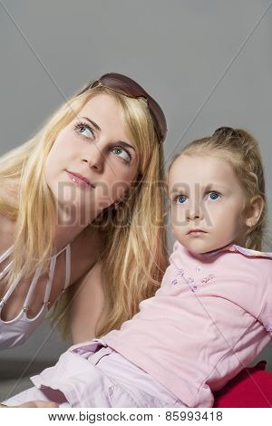 Closeup Portrait Of Young Caucasian Female With Little Daughter Posing Together Embraced. Against Gr