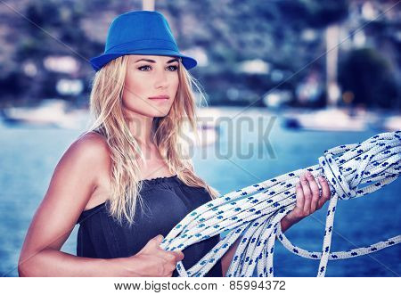 Portrait of beautiful blond female wearing stylish blue hat having fun on sailboat, active lifestyle, enjoying luxury summer vacation