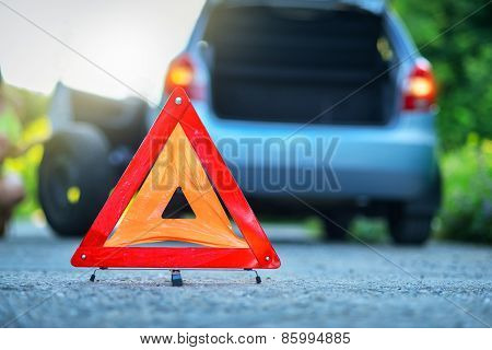 Changing the tire on a broken down car on a road with red warning triangle