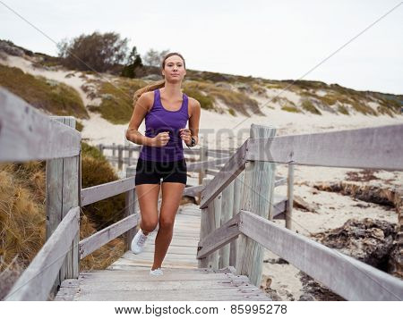 Sporty young woman running up the stairs