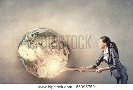 Young businesswoman fixing gears mechanism with wrench. Elements of this image are furnished by NASA