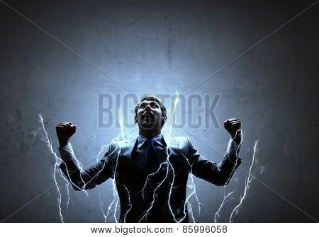 Young powerful businessman n lightning flashes with hands up