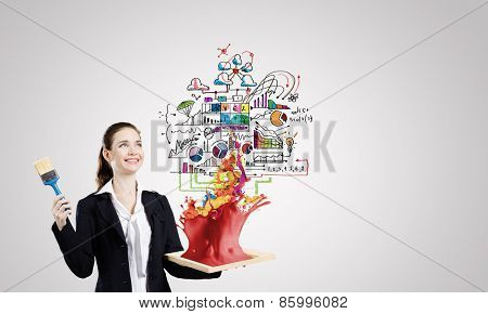 Young businesswoman with paint brush and wooden frame