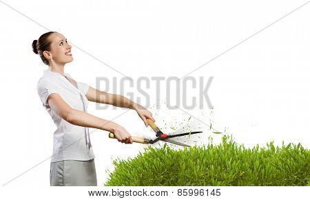 Young attractive businesswoman cutting green lawn. Greenery concept
