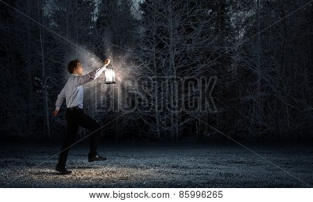 Young businessman walking with lantern in darkness