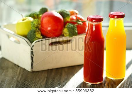 Bottles of juice with fruits and vegetables  in crate on windowsill