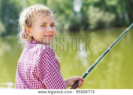 Rear view of cute girl sitting at bank and fishing