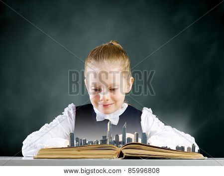 Cute school girl looking in opened book with city model