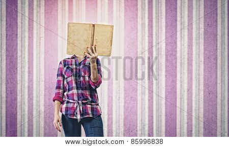 Young woman in casual hiding face behind reading